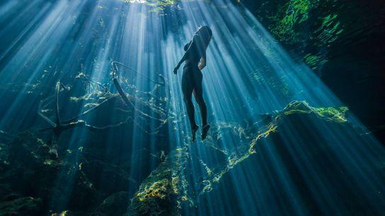 Une nageuse flotte dans les eaux irradiées par le soleil de l'une des nombreuses dolines de ...