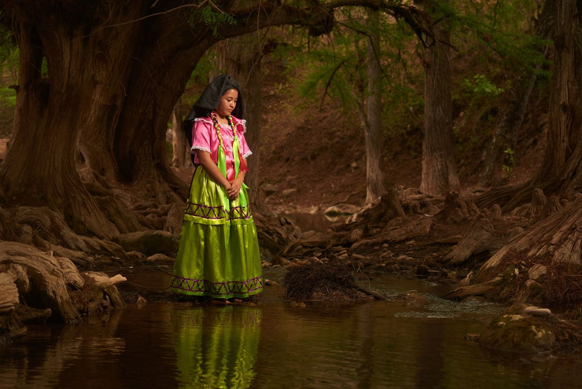 Une femme vêtue d'une robe traditionnelle contemple la rivière d'Ahuehuetes.