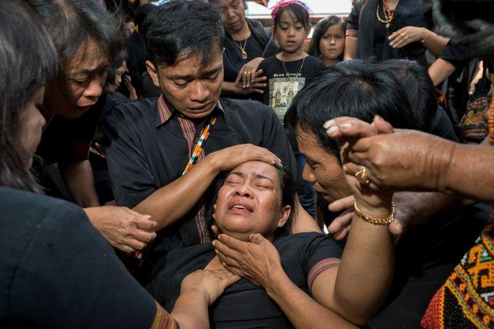 Tini Patiung s'effondre quelques instants avant qu'un groupe d'hommes ne transporte sa mère dans sa tombe. Ester ...