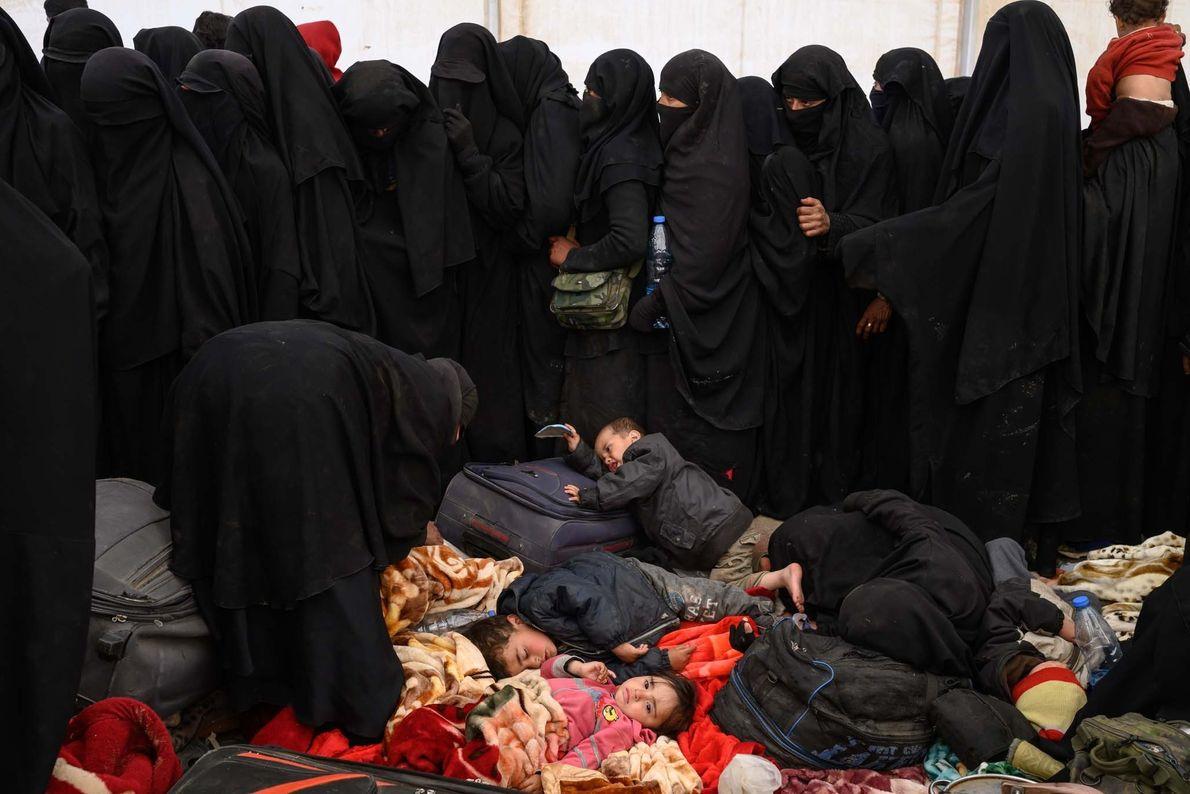 Femmes et enfants qui ont prêté allégeance à l'État islamique, attendent d'être enregistrés dans le camp ...