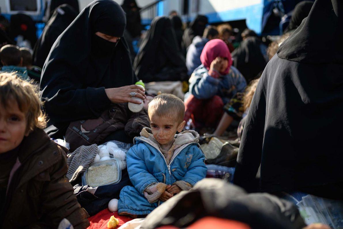 Fatima, un an, regarde sa mère alors qu'elle sort un morceau de pain. Gravement mal nourrie, ...