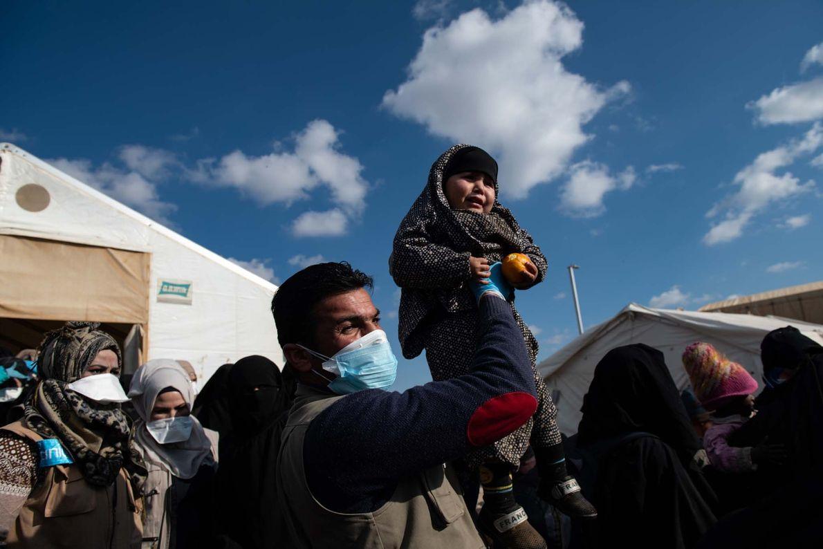 Un travailleur humanitaire tient un enfant égaré dans ses bras alors que des milliers de femmes ...