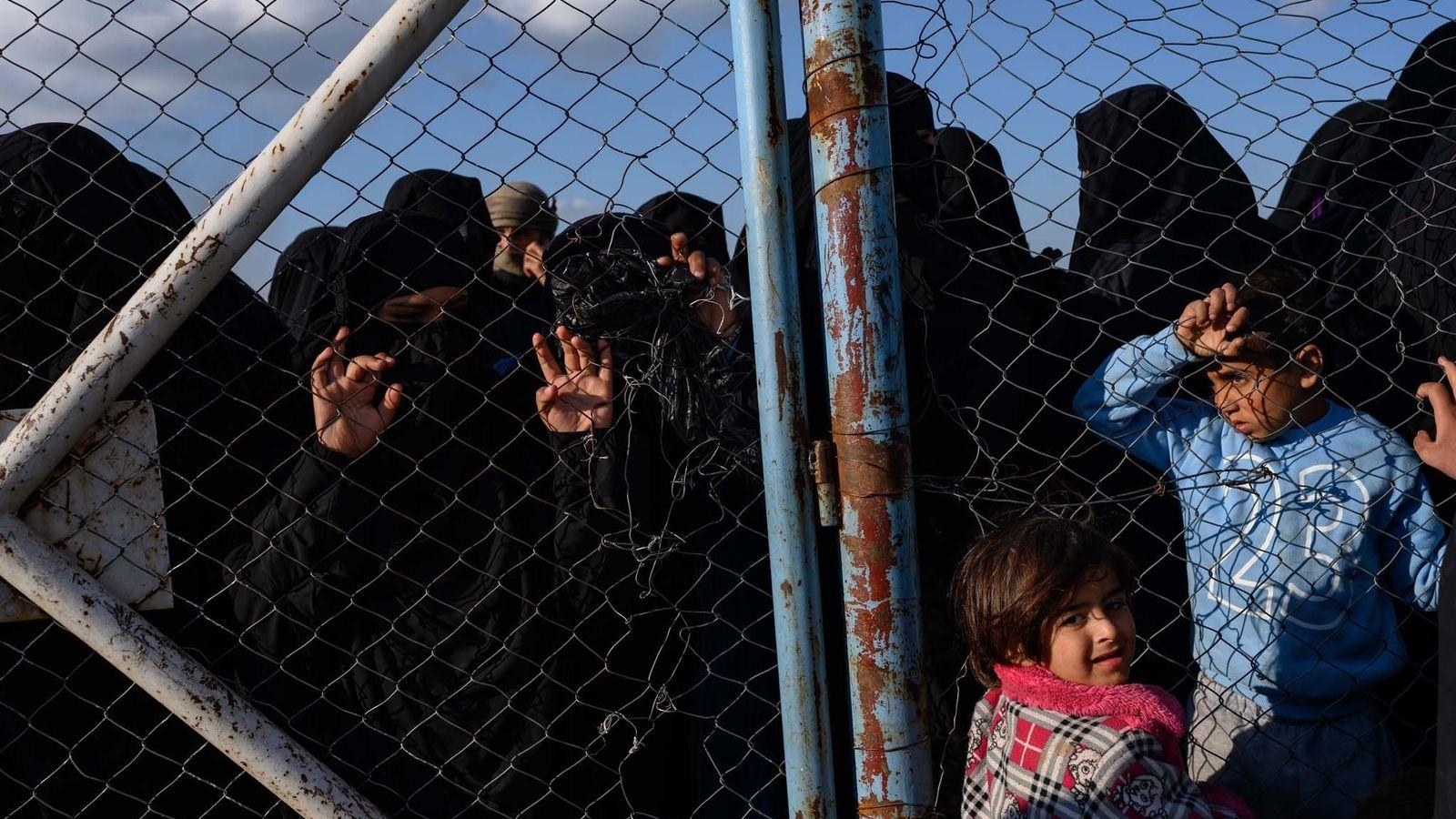 Femmes et enfants, proches des combattants de l'Etat islamique qu'ils continuent de soutenir farouchement, regardent à ...