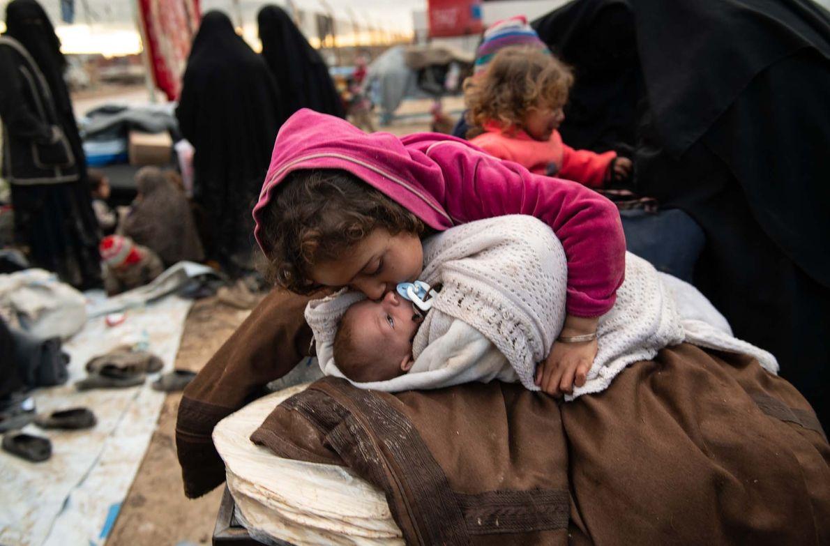 Noor, 7 ans, embrasse son petit frère, Abdullah, âgé d'un mois, alors qu'elle le surveille dans ...