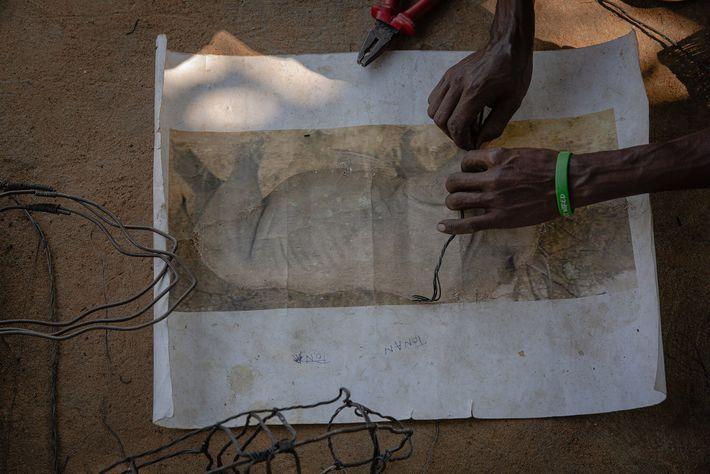 Les artisans de Snares to Wares travaillent sur une sculpture de rhinocéros. Ils ont mis en ...