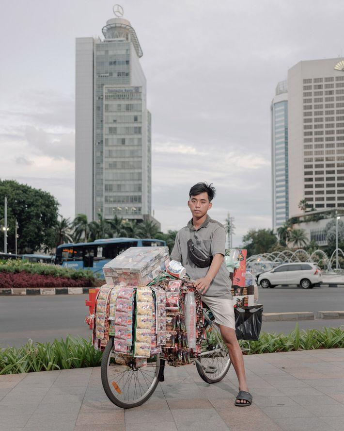 Fauzi, un travailleur informel, vend du café soluble près de l'hôtel Indonesia Roundabout, au cœur d'une ...