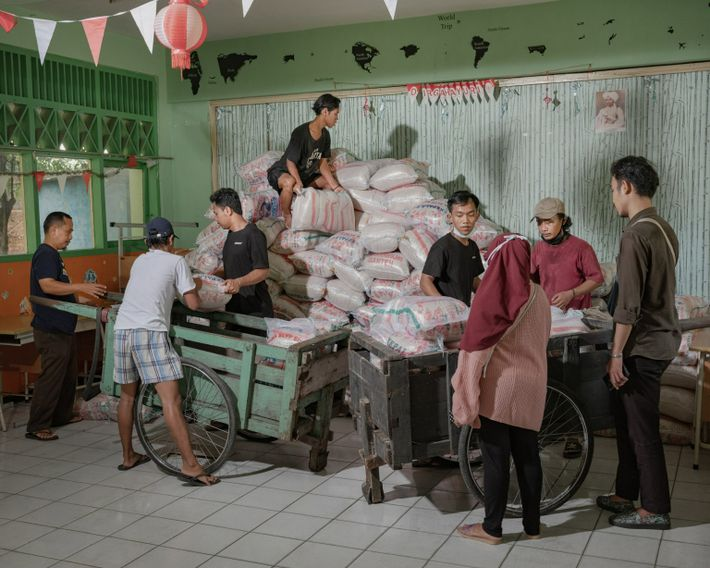 Les bénévoles de la Foodbank of Indonesia déchargent et entreposent 20 tonnes de sacs de riz dans ...