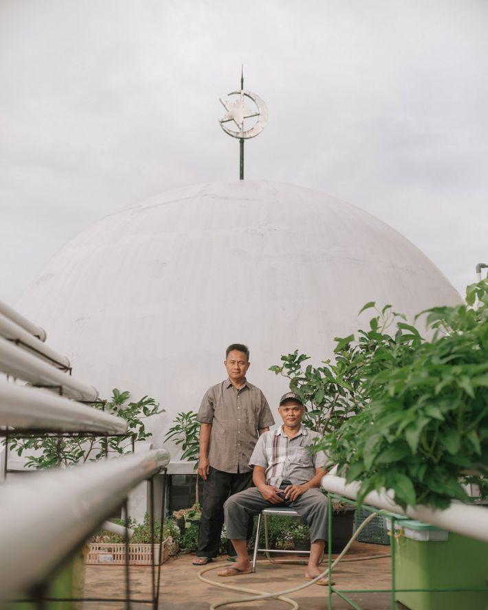 Yono (à gauche) et Faizin prennent la pose devant les plantes de leur serre installée sur ...