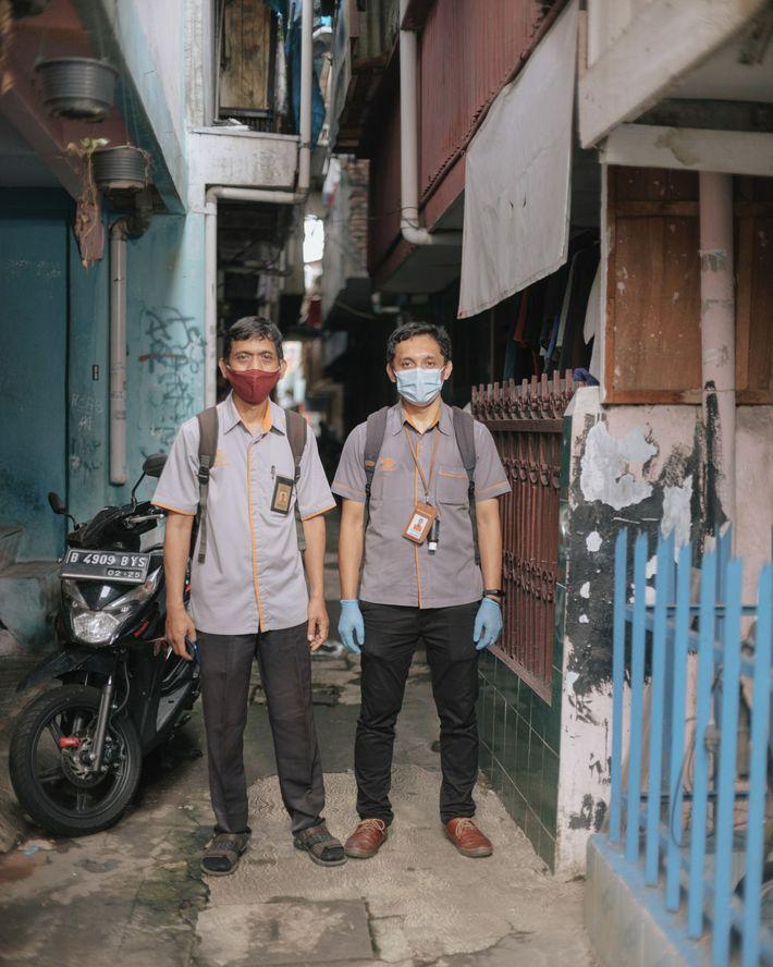 Employés du service postal indonésien, Mustofa (à gauche) et Alfian sont en train de distribuer les ...