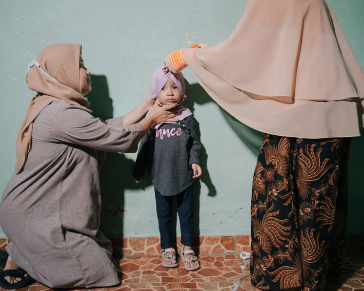 Roozmalinie (à gauche) et sa fille de 3 ans, Aquilla (au centre), ici mesurée par Kris Wati ...