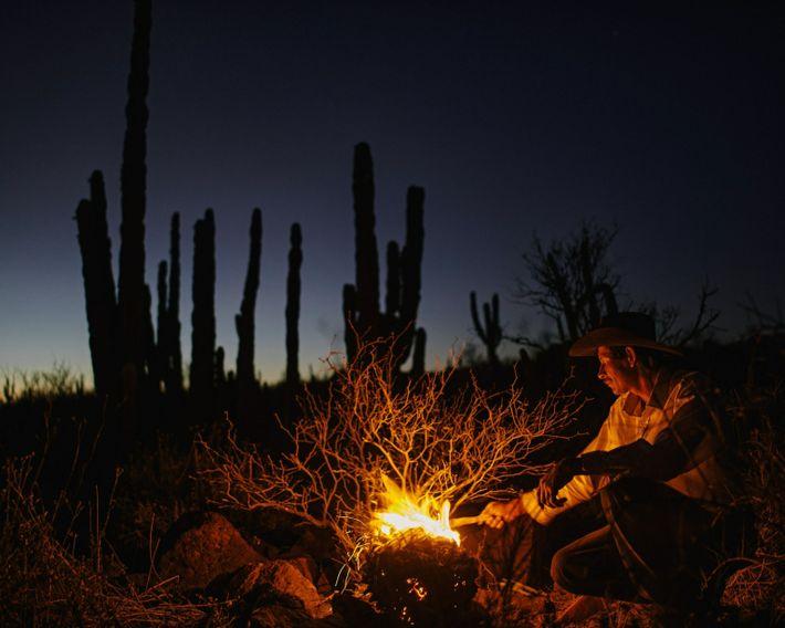 Nary allume un feu tandis qu'il déplace ses animaux à la recherche de végétation près du ...