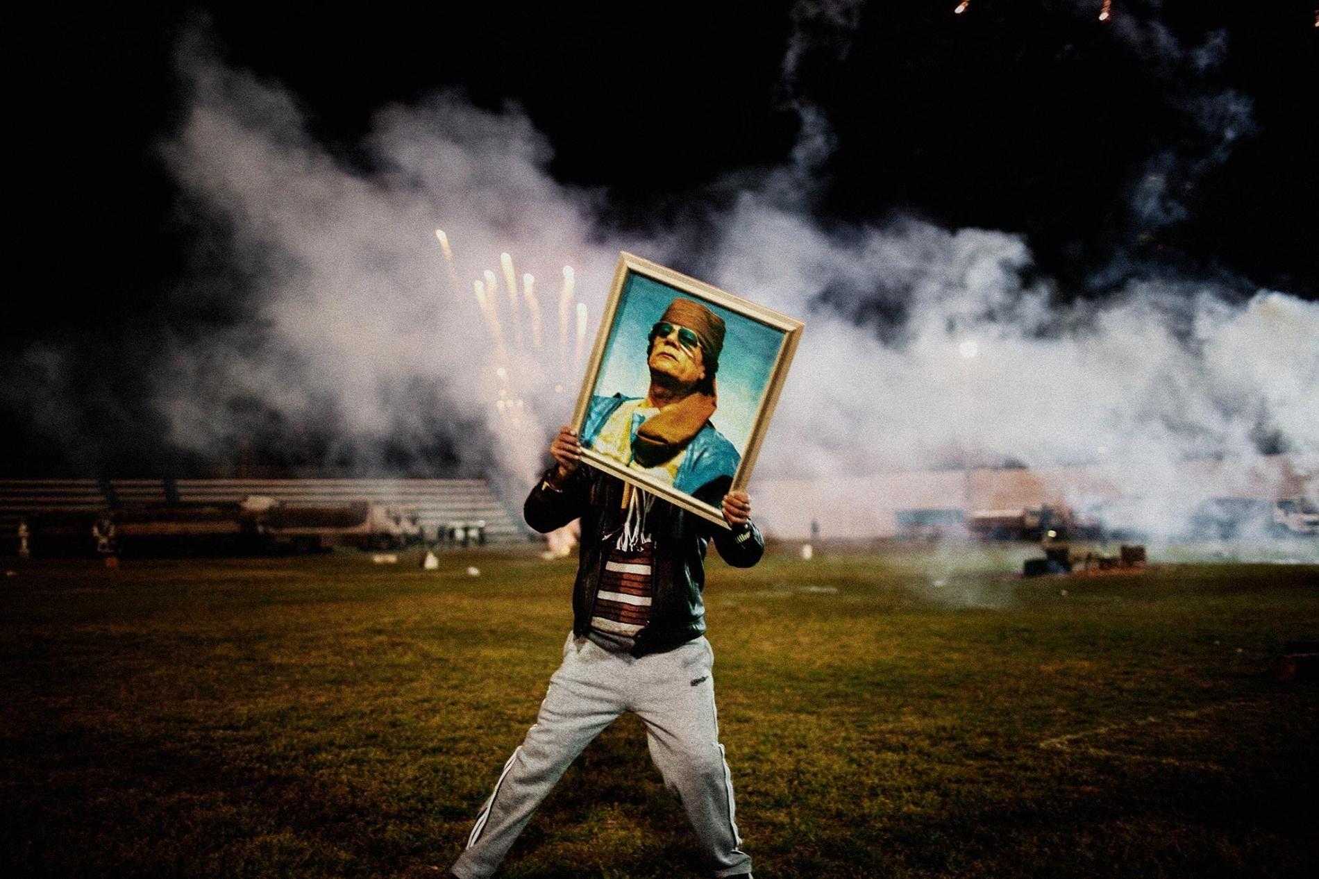 Un partisan de Kadhafi porte le portrait du leader libyen lors d'une célébration organisée à l'occasion de la visite d'un groupe de journalistes étrangers, après la reprise de la ville aux mains des rebelles par les forces du régime. Zawiyah, Lybie. Mars 2011