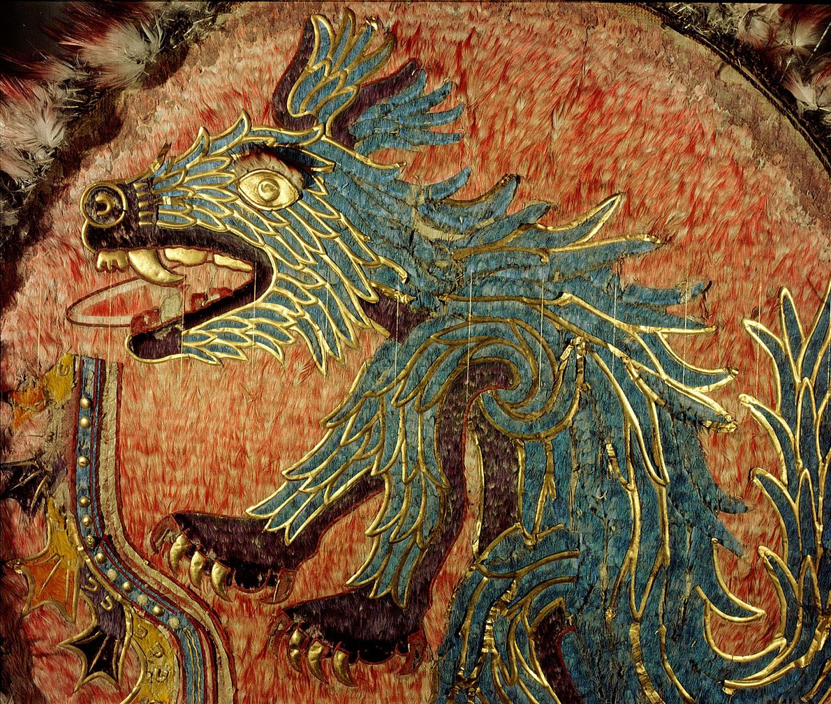 La créature bleue serrant dans sa gueule un poignard qui décore ce bouclier de cérémonie en ...