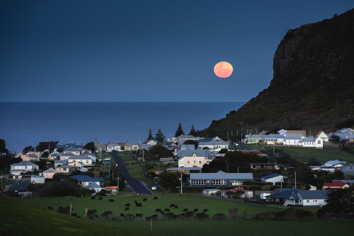 Une énorme lune d'automne flotte dans le ciel au-dessus des maisons de campagne et des pâturages ...