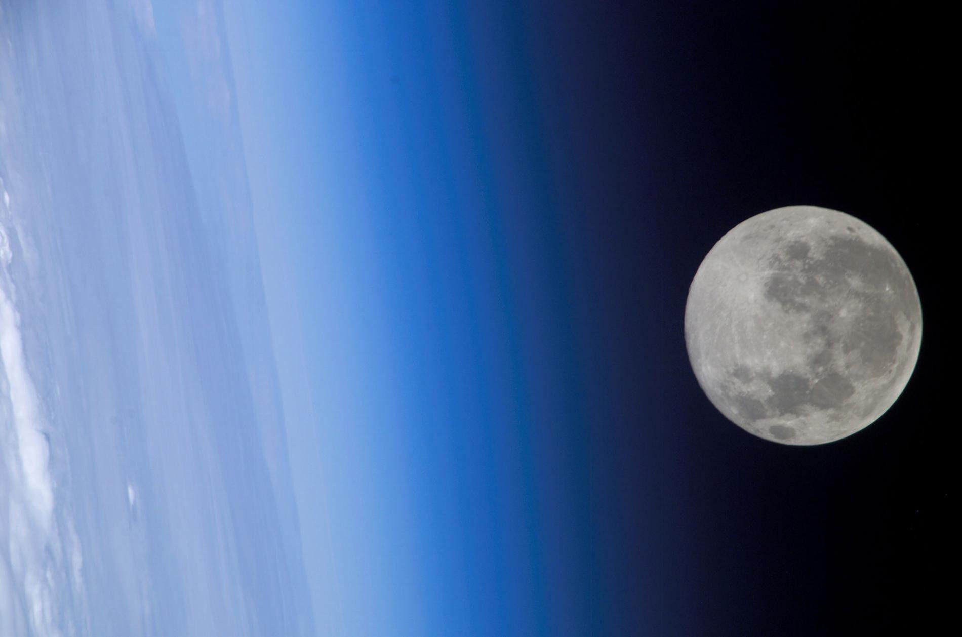 Vue depuis la Station spatiale internationale, la pleine lune semble effleurer l'atmosphère de la Terre.