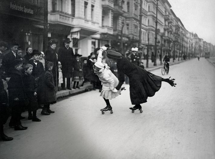 Des passants observent une femme et une jeune fille patiner dans une rue de Berlin, sur ...