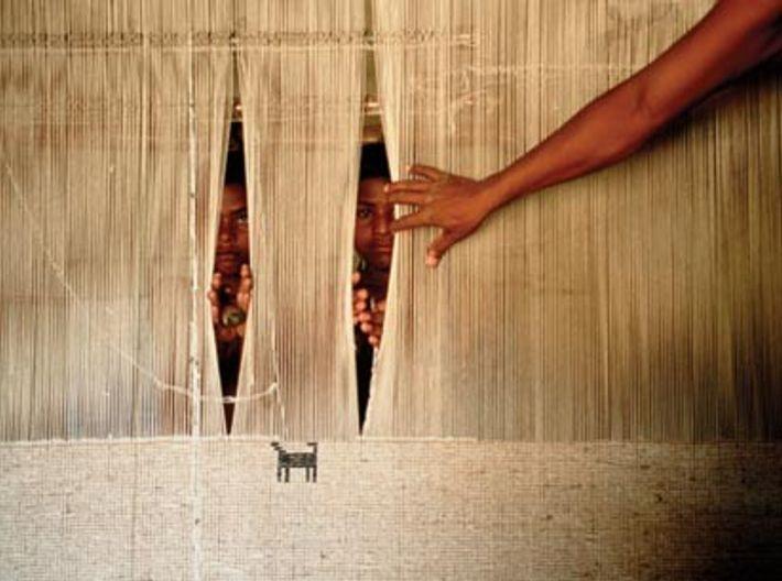 De jeunes garçons passent un œil dans une toile tendue, en Inde. Plus de 300 000 ...
