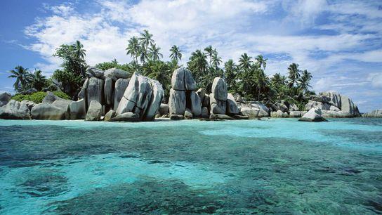 Les roches granitiques et les palmiers créent le paysage idyllique des îles des Seychelles.