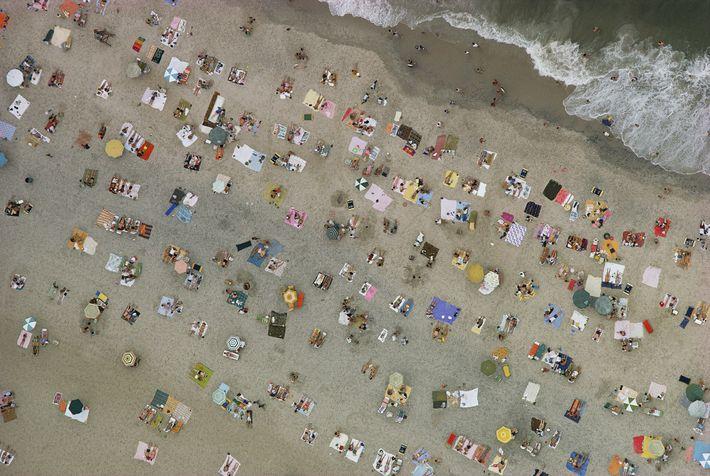 Sur cette vue aérienne de 1967, un parterre de baigneurs se relaxe sous les parasols ou ...