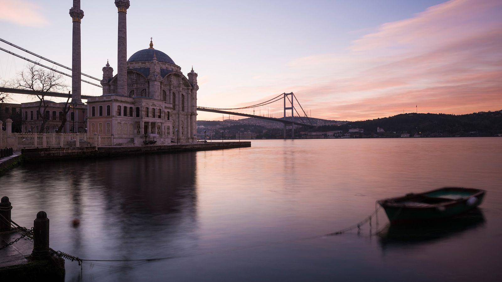 L'aube se lève sur la mosquée d'Ortaköy à Istanbul en Turquie, teintant le ciel de rose. ...