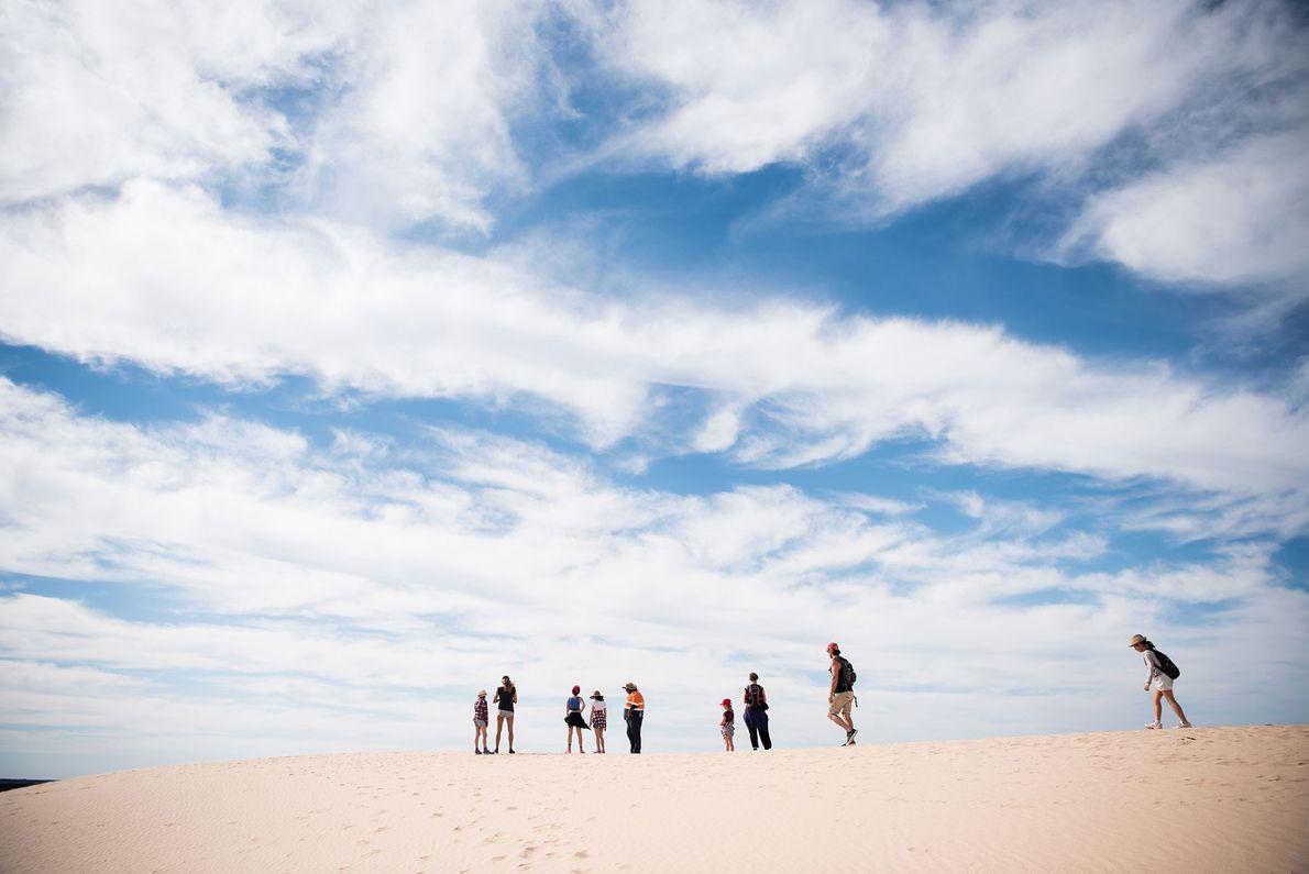 Un guide aborigène mène un groupe dans les murs de Chine et dans les dunes du ...
