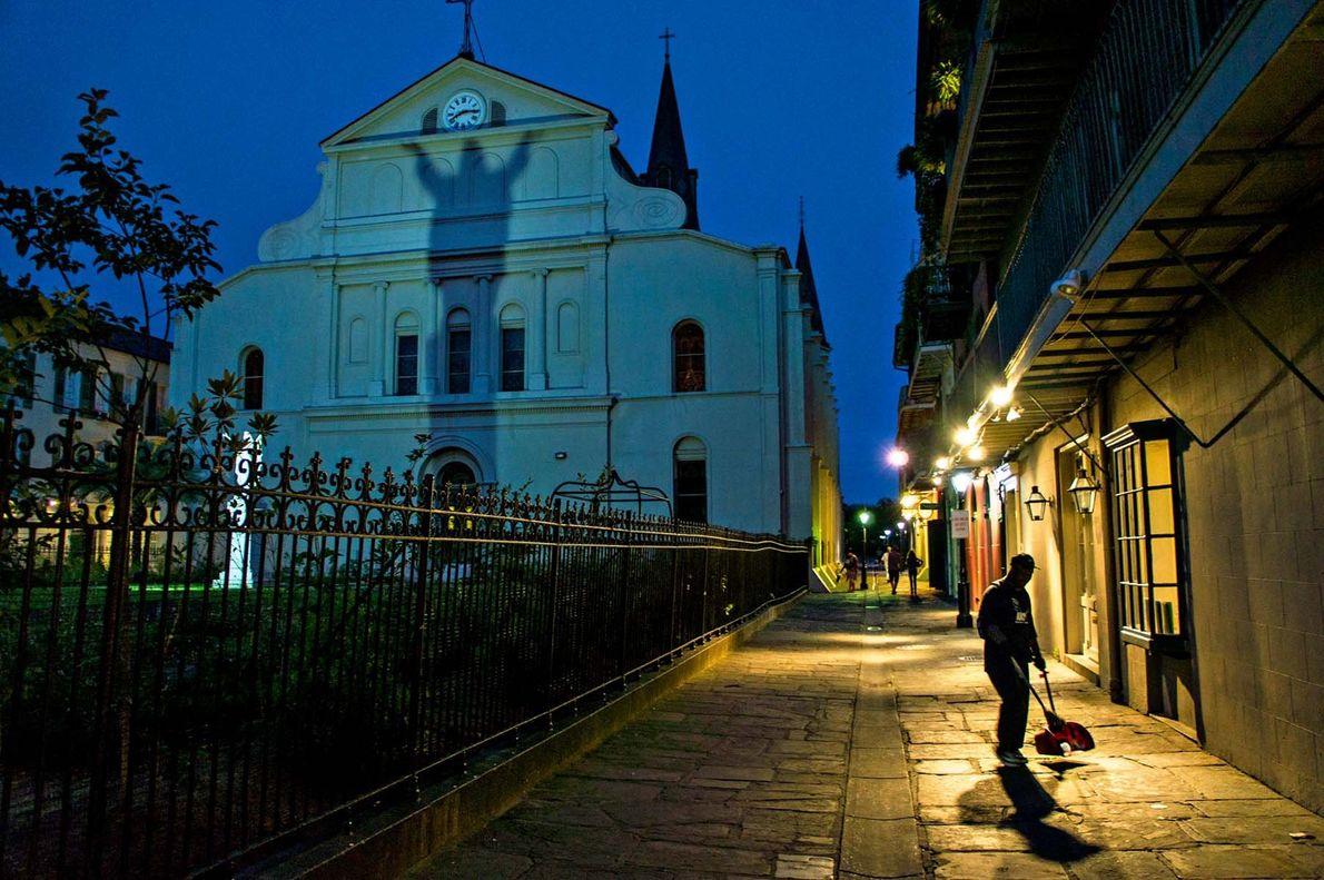 Un homme balaie la rue à la lumière des lampadaires près de la cathédrale Saint-Louis de ...
