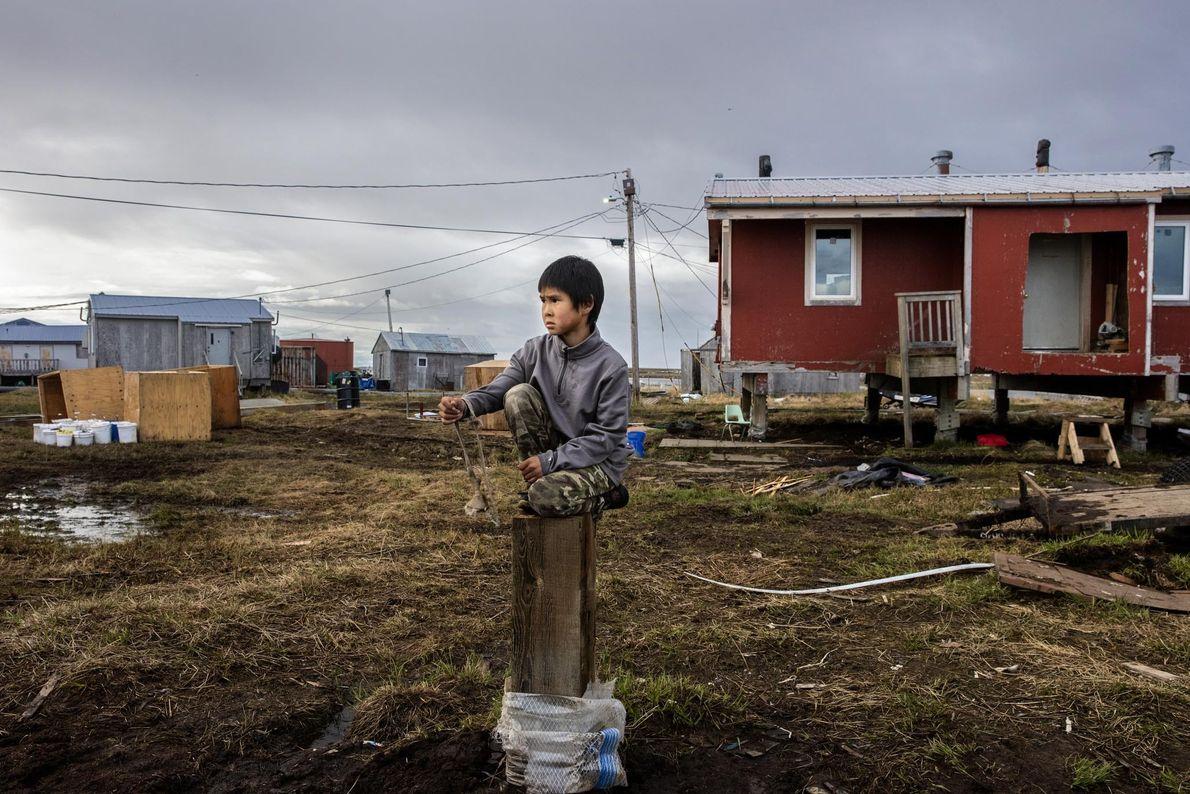 Reese John joue avec son lance-pierre assis sur le pilotis d'une maison de Newtok récemment démolie. ...