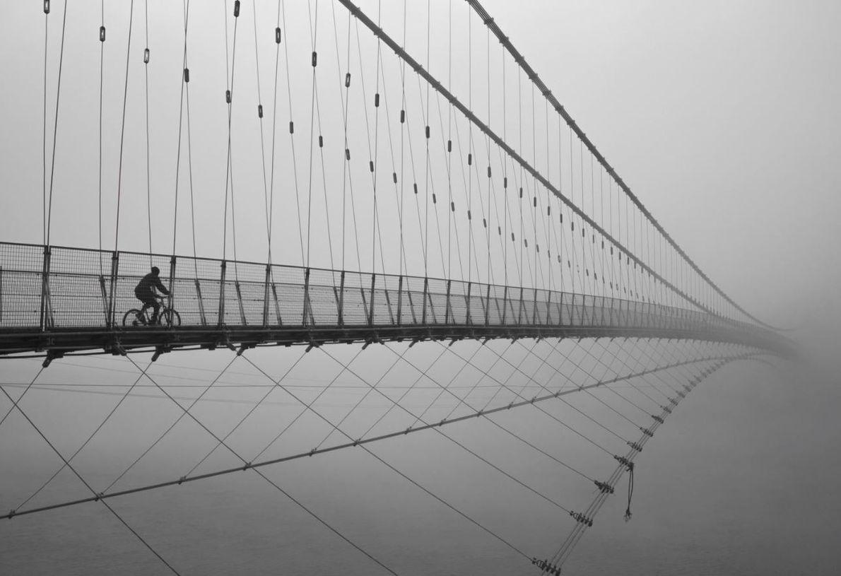 CATÉGORIE PHOTOGRAPHIE URBAINE - Un voyageur est vu traversant le pont Ram Jhula en Inde. Sur ...