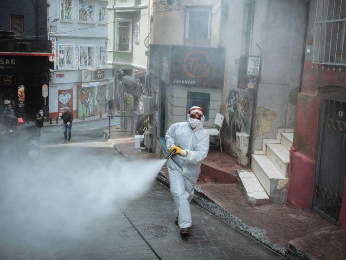 Sur le front d'une crise mondiale. Istanbul, Turquie. Un employé municipal désinfecte une rue du quartier d'ordinaire ...