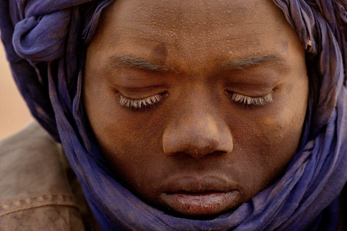 Le visage couvert de sable, cet adolescent sort tout juste de la mine où il travaille. ...