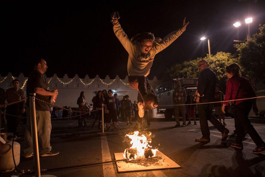 De jeunes gens sautent par-dessus les flammes pour s'attirer la bonne fortune, lors de cette commémoration ...