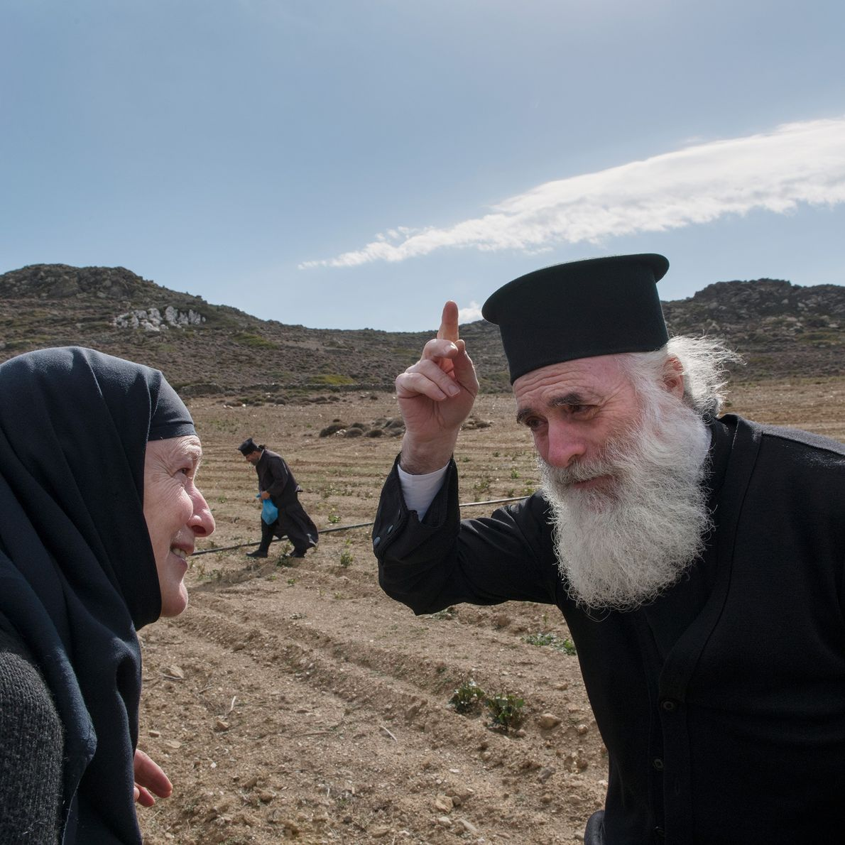 Sœur Irini discute avec le père Georgios Theologitis, grand prêtre d'Amorgos, dans un champ non loin ...