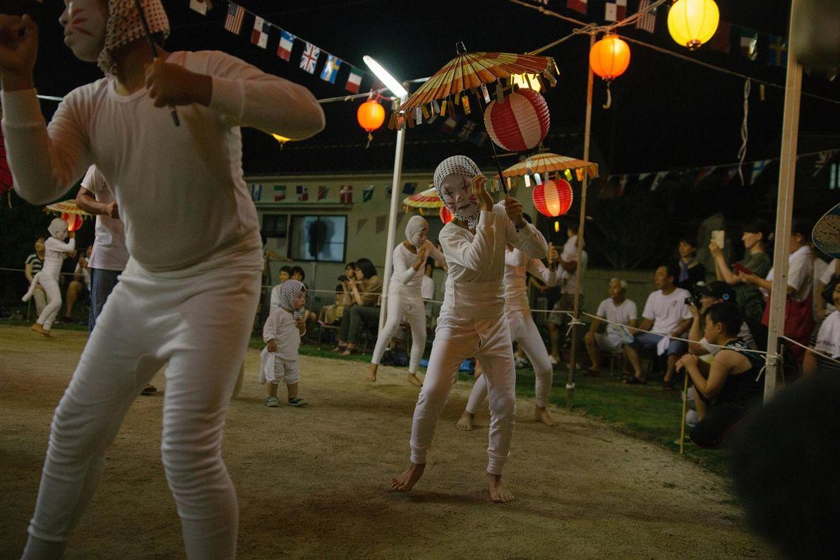 Un groupe de kitsune interprète la danse du O-bon au rythme d'un tambour. Les gens se ...