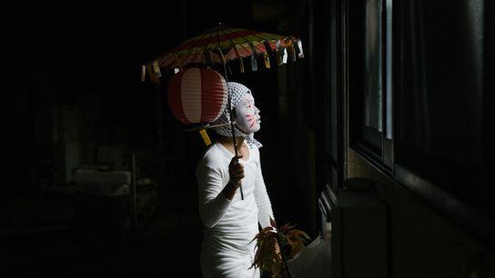 Un enfant habillé en kitsune, c'est-à-dire en renard, regarde dans la maison d'un voisin pendant le ...