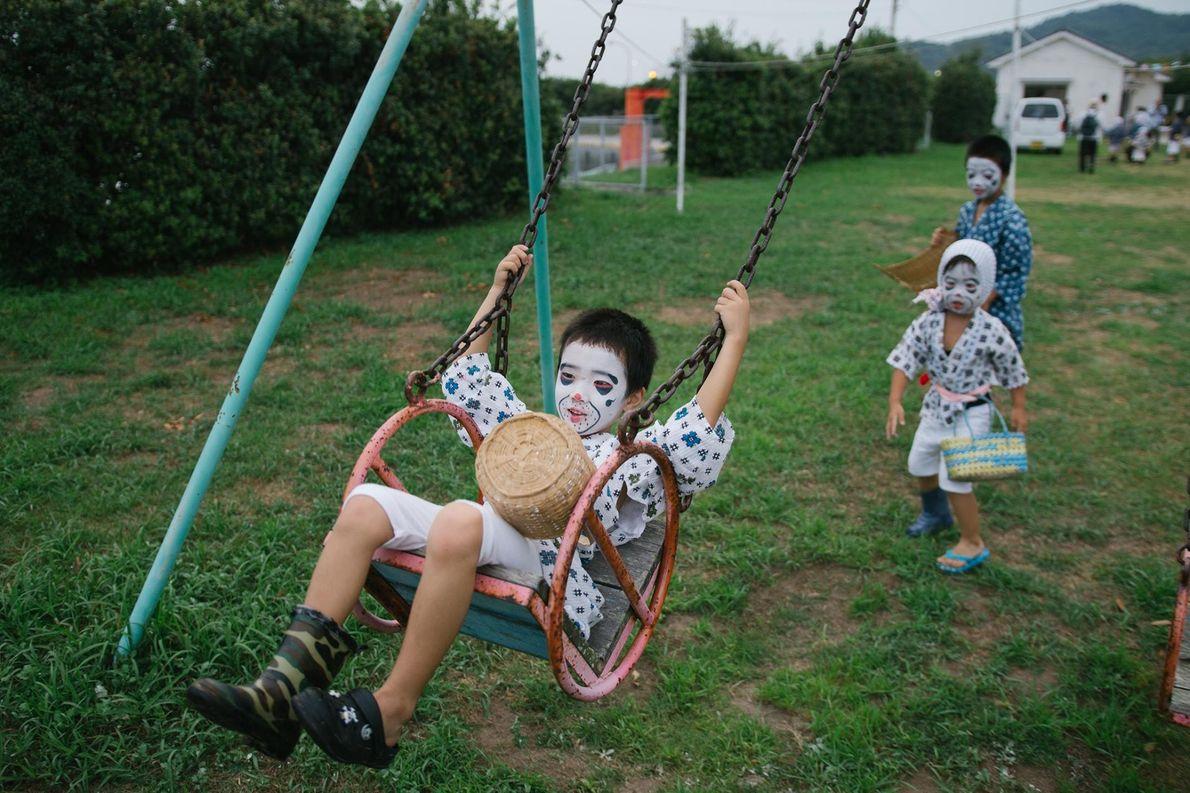 Des enfants déguisés en « pêcheurs ivres » jouent dehors pendant le festival du O-bon.