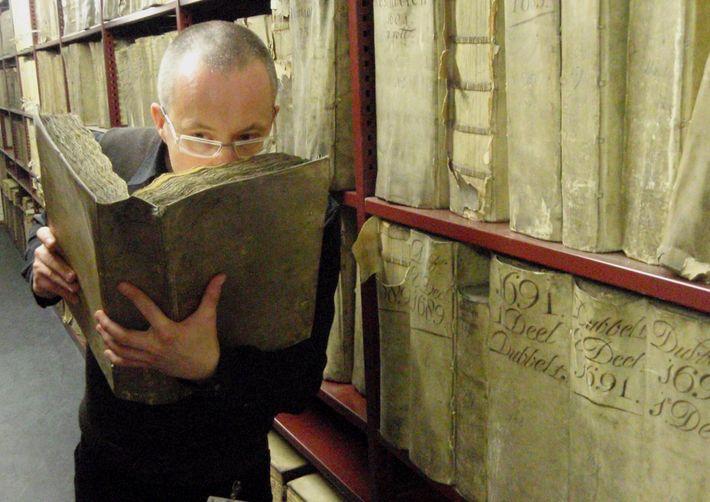 Le professeur Matija Strlic sentant un livre historique aux Archives nationales des Pays-Bas