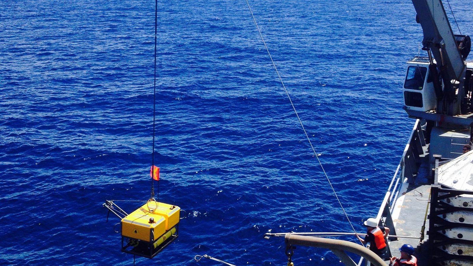 Les scientifiques à bord du navire oécanographique Thomas G. Thompson récupèrent un sismomètre qui enregistraient les ...