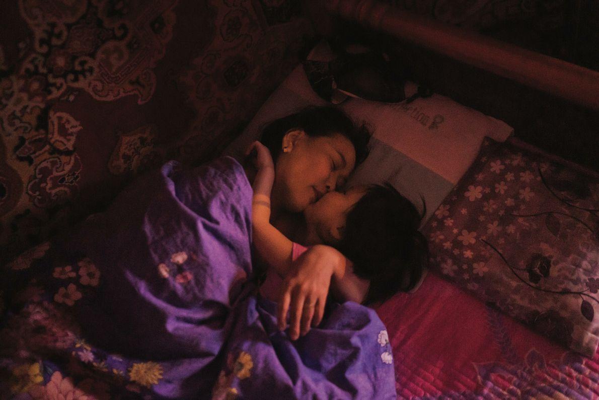 Altanzul Sukhchuluun et sa fille, Khulan, blotties l'une contre l'autre à l'heure du coucher à Oulan-Bator. ...