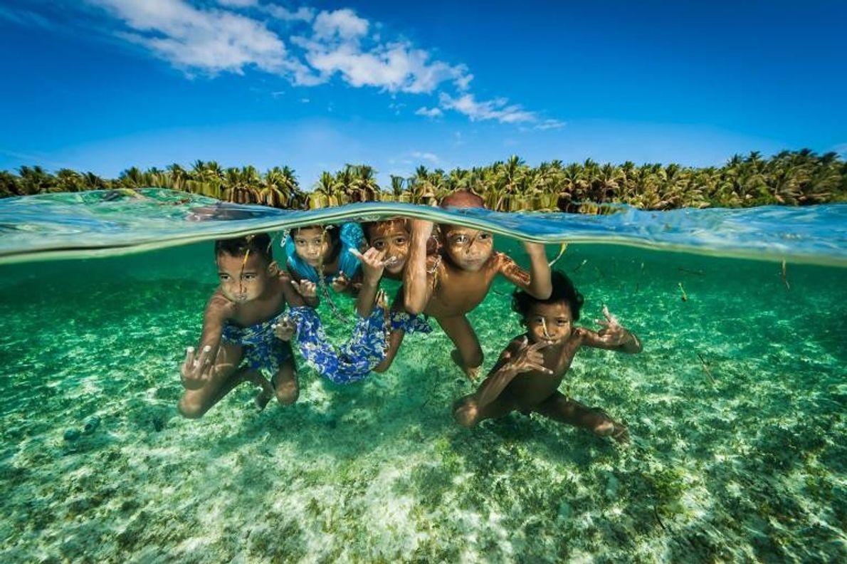 Des descendants des légendaires navigateurs de l'île de Satawal s'amusent dans les eaux tièdes des îles ...