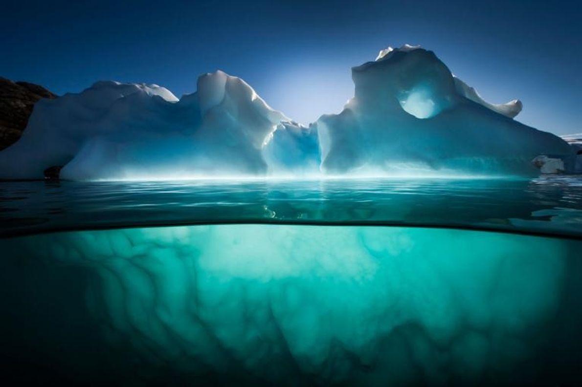 Non loin de l'île Red, dans le fjord Scoresby Sund, au Groenland, un iceberg scintille sous ...