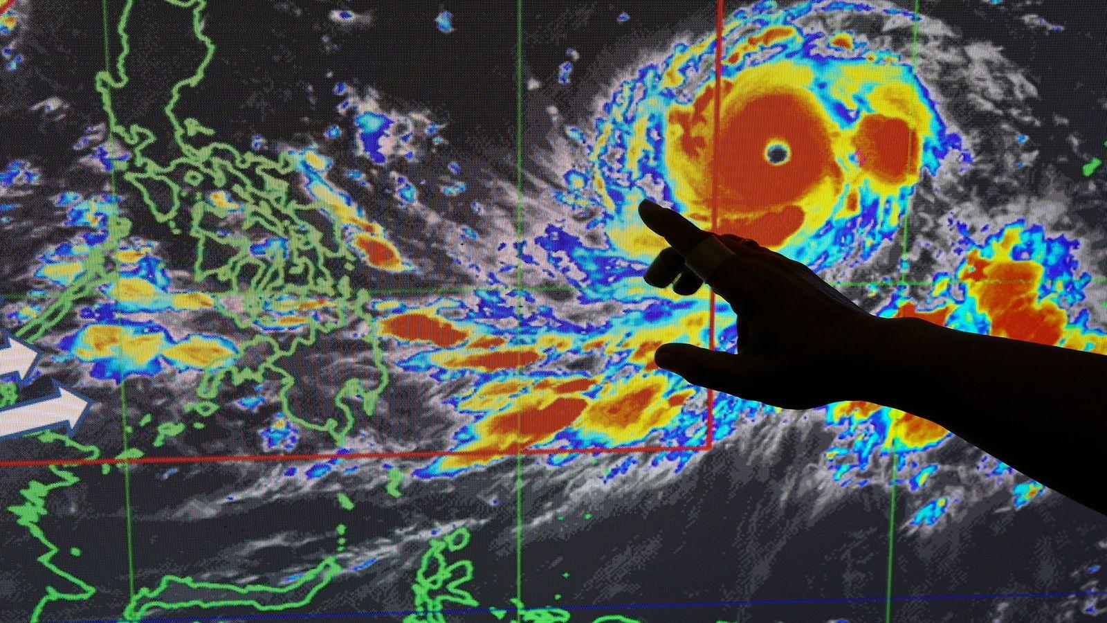 À Manille, le météorologue Meno Mendoza montre le parcours du super-typhon Mangkhut, appelé également typhon Ompong ...