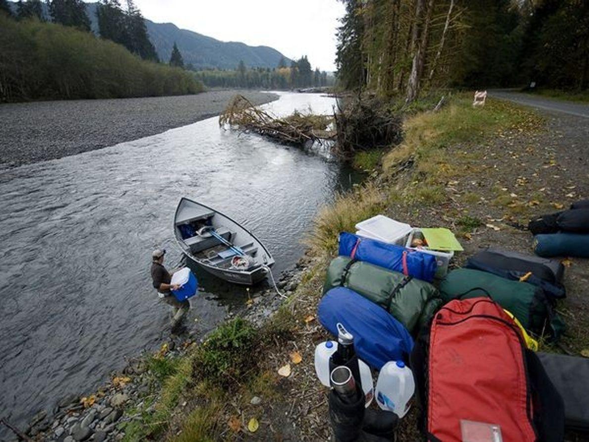 Photo de campeurs se préparant pour une session de pêche à la mouche dans la rivière ...