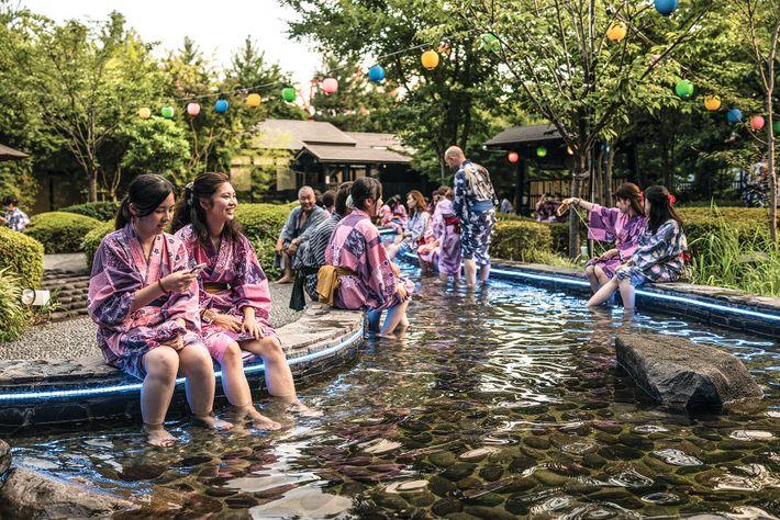 Des visiteurs se délassent les pieds dans un bassin tapissé de galets à Oedo-Onsen Monogatari, un ...