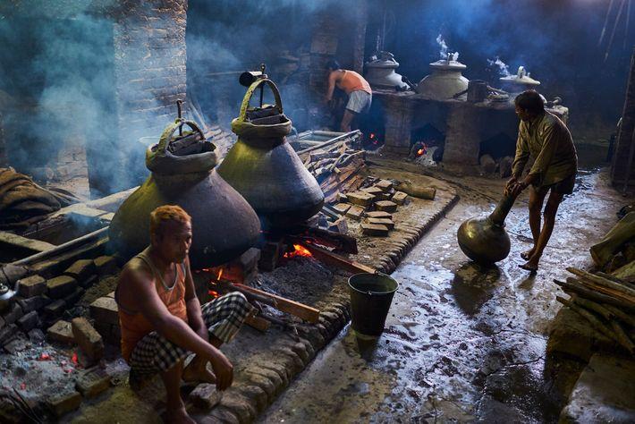 Une fois les alambics en cuivre scellés par les ouvriers, les fleurs sont bouillies. La vapeur ...