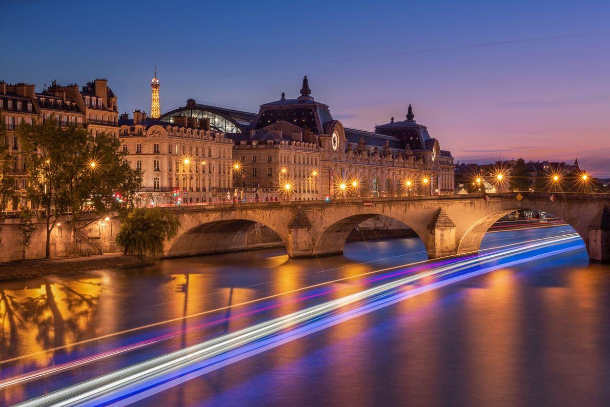La flèche de la tour Eiffel s'illumine derrière le musée d'Orsay alors que des bateaux font ...
