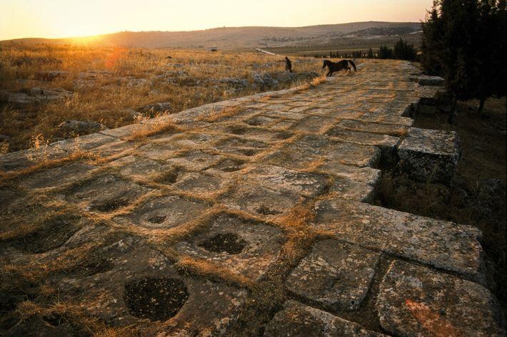 Une voie romaine pavée traverse le paysage près de l'actuelle ville d'Alep, en Syrie. Elle fut ...