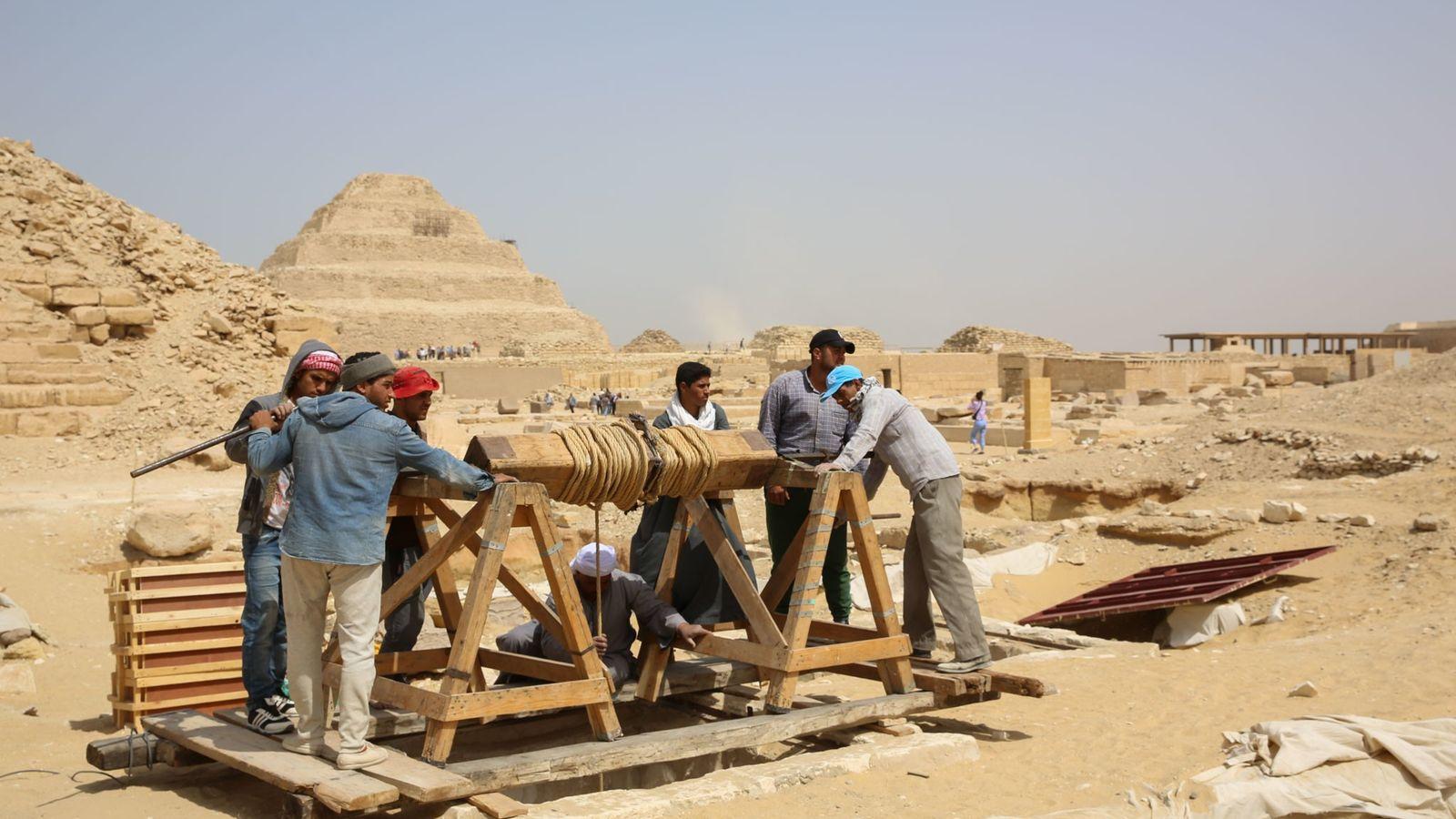 Des ouvriers acheminent vers le site de fouilles des outils 30 mètres plus bas, là où ...