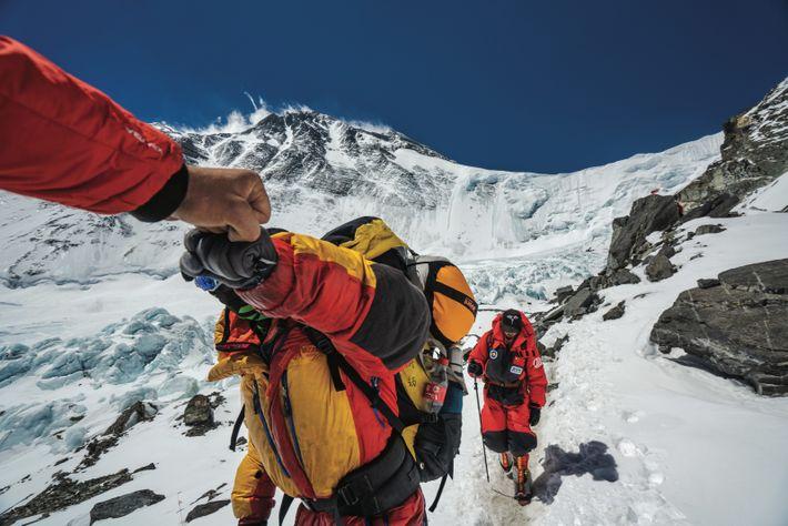 Le photographe Renan Ozturk fait un check avec un alpiniste qui retourne au camp de base ...