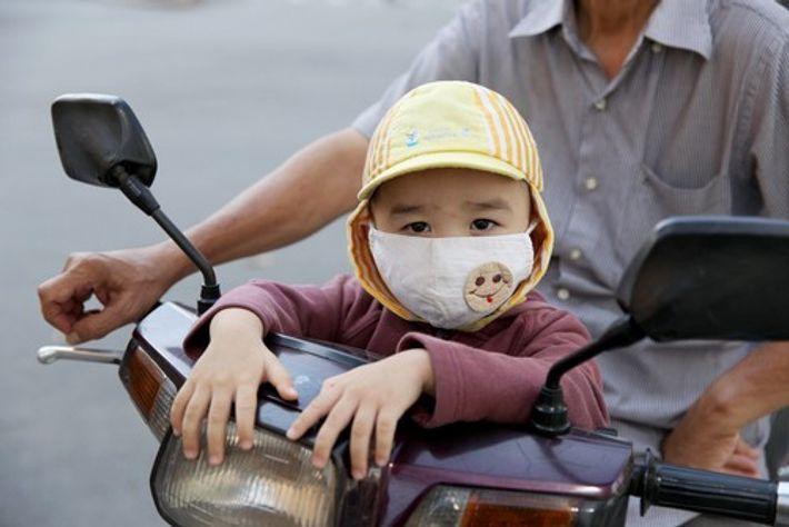 Un jeune enfant porte un masque pour le protéger de la pollution.