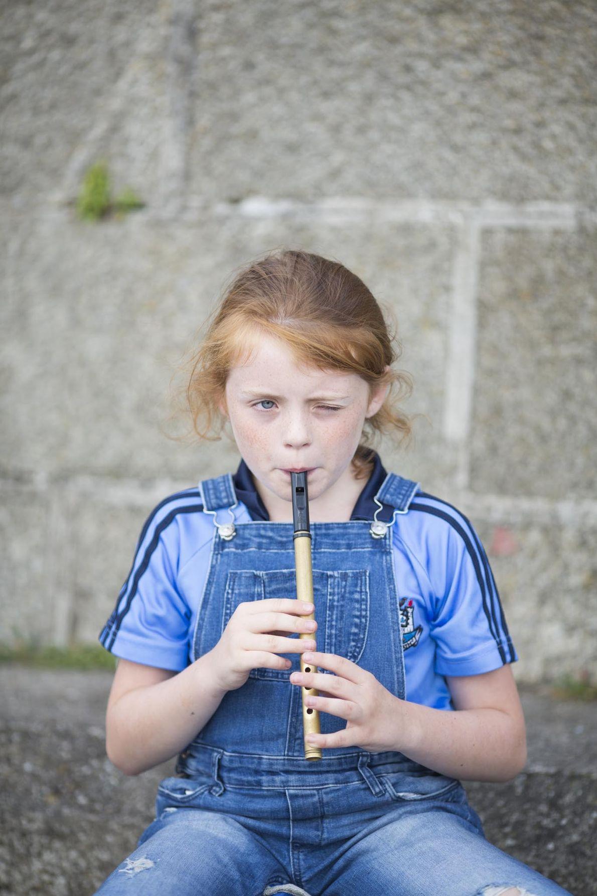 Une petite fille joue de la flûte irlandaise en face du port dans le village de ...